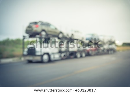 Blurred image big car carrier truck of new cars for batch delivery to dealership. Full load transport truck of new vehicles on country road. Automotive industry abstract background.Vintage filter look #460123819