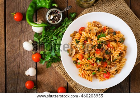 Vegetarian Vegetable pasta Fusilli  with zucchini, mushrooms and capers in white bowl on wooden table. Top view #460203955