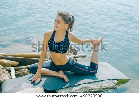 young woman is engaged in meditation, stretching, yoga on the beach background #460229500