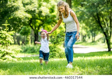 Little boy with mom and dad playing in the park. #460317544