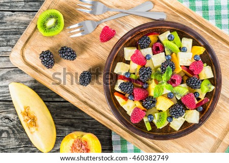 delicious fruit and berry summer salad decorated with mint leaves on clay dish on cutting board with dessert forks, half of peach and slice of melon on rustic boards, view from above #460382749