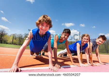 Happy teenagers holding plank outdoor on the track #460504207