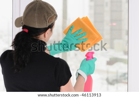 The woman in a cap and green gloves washes a window #46113913