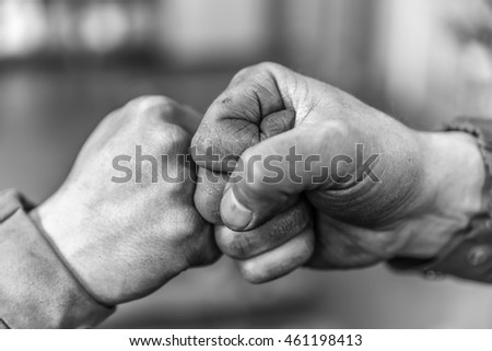 Two fellow workers greeting each other with a handshake using their fists as a symbol of companionship, friendship and solidarity. #461198413