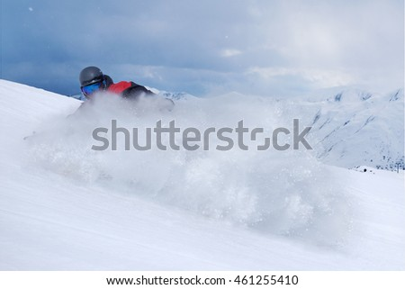 Snowboarder riding fast on a dry snow on freeride slope. #461255410