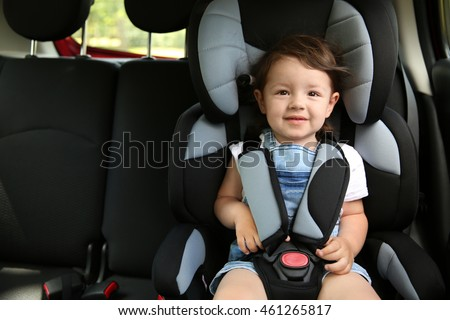 Boy sitting in a car in safety chair #461265817