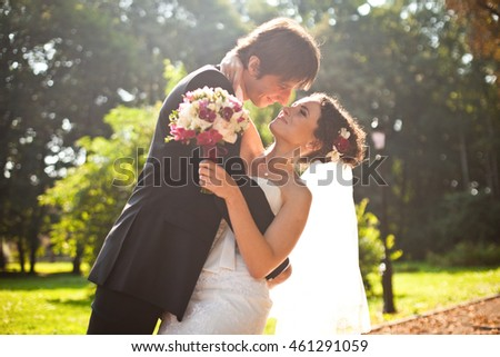 Warm picture of sweet wedding couple posing in the park