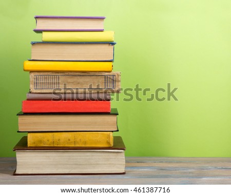 Books on grunge wooden table desk shelf in library. Back to school background with copy space for your ad text. Old hardback books with no labels, blank spine #461387716