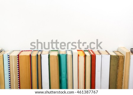 Books on grunge wooden table desk shelf in library. Back to school background with copy space for your ad text. Old hardback books with no labels, blank spine #461387767