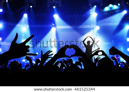 Singer on concert stage with ray of illuminated and crowd of cheering fans in music concert #461525344