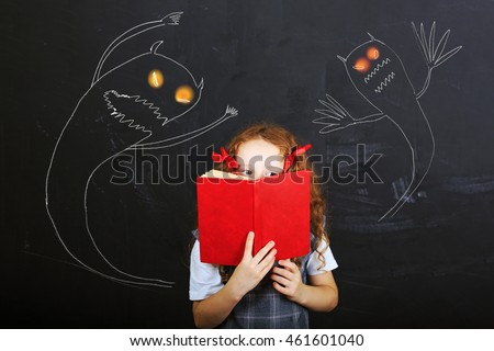 Child hiding behind the book, and is afraid near chalkboard. Education concept.