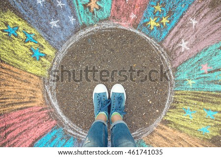 Comfort zone concept. Feet standing inside comfort zone circle surrounded by rainbow stripes painted with chalk on the asphalt. Royalty-Free Stock Photo #461741035