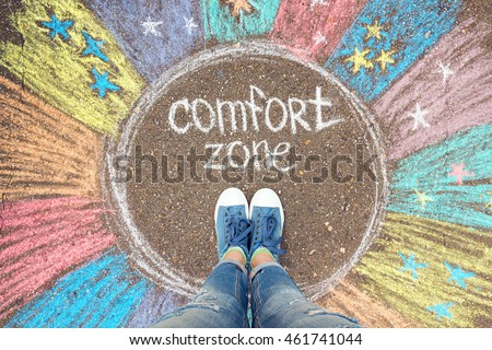 Comfort zone concept. Feet standing inside comfort zone circle surrounded by rainbow stripes painted with chalk on the asphalt. #461741044