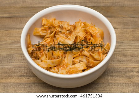 pasta  fettuccine bolognese in  dish on brown wooden table #461751304