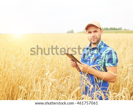 Farmer in a plaid shirt controlled his field and working at tablet.  Wheat harvest. Agriculture. #461757061