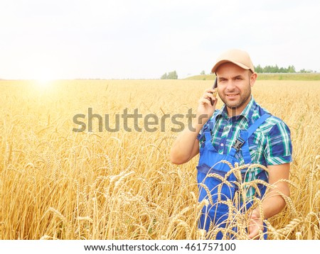 Farmer in a plaid shirt controlled his field. Talking on the phone. Wheat harvest. Agriculture. #461757100