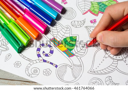 Woman coloring the coloring book for adults with abstract patterns, colored pens, antistress painting