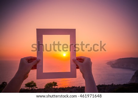 A hand is holding up a blank photo snapshot at a sunny beach. Add your message in the area. Instagram filter effect. Inspirational summer beach background concept.