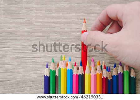 Hand choosing a colored pencil on wooden background. #462190351