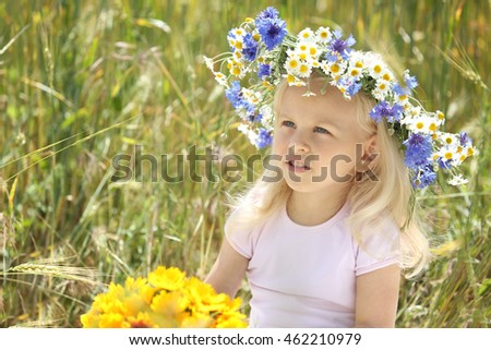 Little blonde girl with wreath in the field #462210979
