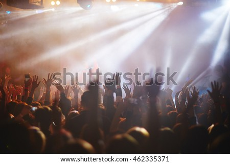Silhouettes of concert crowd in front of bright stage lights #462335371
