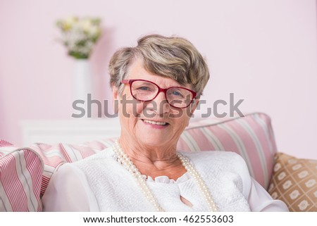 Portrait od smiled senior woman sitting on a couch with pillows #462553603