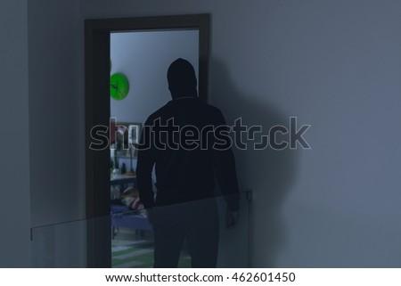Masked burglar looking into a kid's room through an open door #462601450