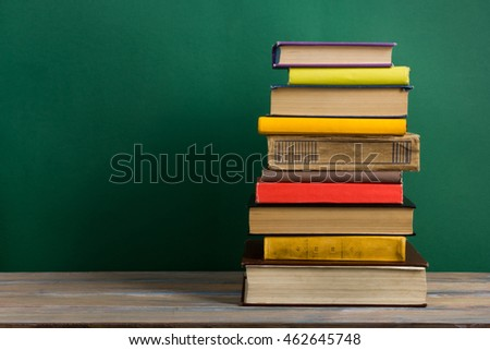 Colorful composition with vintage old hardback books, diary on wooden deck table and green background. Books stacking. Back to school. Copy Space. Education background #462645748