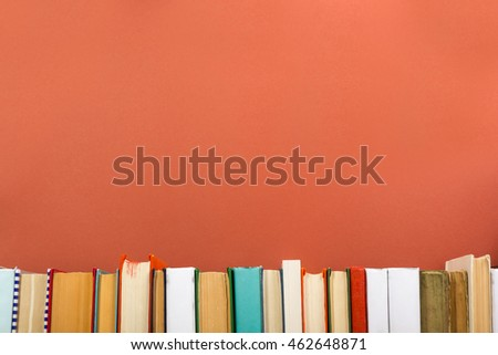 Colorful composition with vintage old hardback books, diary on wooden deck table and red background. Books stacking. Back to school. Copy Space. Education background #462648871