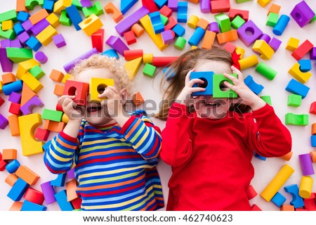 Happy preschool age children play with colorful plastic toy blocks. Creative kindergarten kids build a block tower. Educational toys for toddler or baby. Top view from above. Royalty-Free Stock Photo #462740623