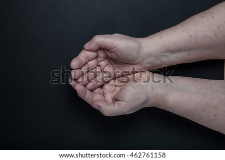 Hands of elderly woman on black background. Toned. #462761158