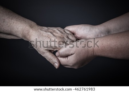 Hands of elderly and young women on black background. Toned. #462761983