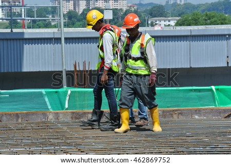 MALACCA, MALAYSIA -JULY 23, 2016: Construction workers wearing safety harness belt at other safety gear during working at the construction site area.   #462869752