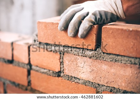 Close up of industrial bricklayer installing bricks on construction site Royalty-Free Stock Photo #462881602