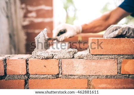 Bricklayer worker installing brick masonry on exterior wall with trowel putty knife #462881611