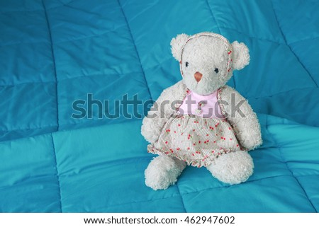 it is soft bear doll sitting on bed. #462947602