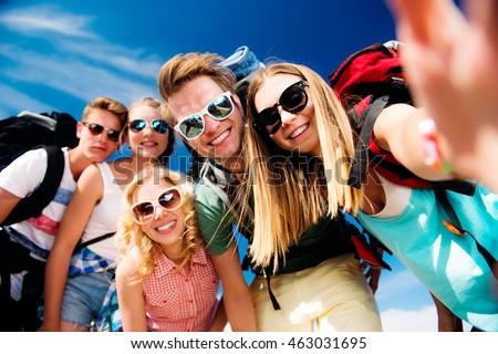 Teenagers with backpacks taking selfie, summer festival