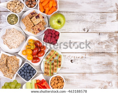 Healthy snacks on wooden table with copy space, top view Royalty-Free Stock Photo #463188578