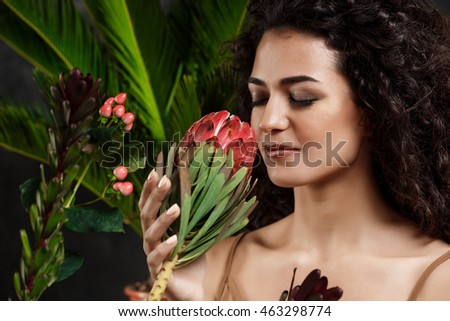 Young beautiful brunette girl in tropical plants over grey background. #463298774