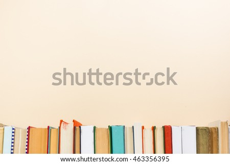 Colorful composition with vintage old hardback books, diary on wooden deck table and beige background. Books stacking. Back to school. Copy Space. Education background #463356395