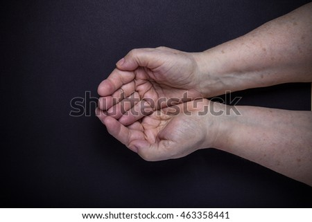 Hands of elderly woman on black background. Toned. #463358441