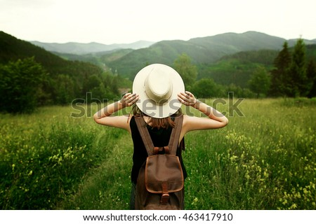 woman traveler with backpack holding hat and looking at amazing mountains and forest, wanderlust travel concept, space for text, atmospheric epic moment Royalty-Free Stock Photo #463417910
