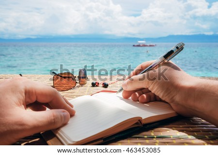 caucasian man is writing sime idea, message or letter in his notepad by pen while he sitting on the beach of tropical sea with boat
