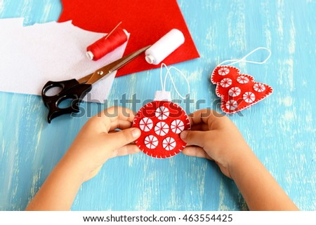Child holds a Christmas tree ball in his hands. Embroidered red and white ball ornament. Felt sheets, thread, needle, scissors on a blue wooden background. Child doing Christmas crafts #463554425