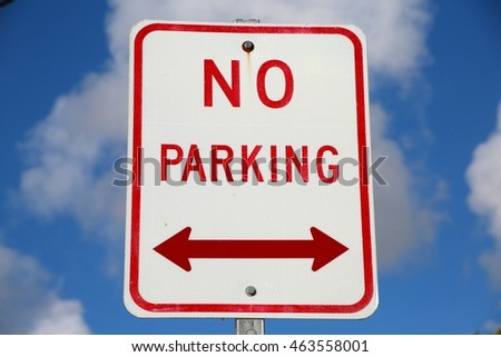 Red and White No Parking Sign with Double Bi-Directional Arrow Against Partly Cloudy Blue Sky