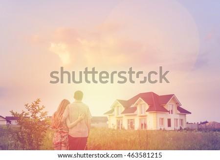 Young Couple Standing Outside Dream Home in sunset. Copy space #463581215