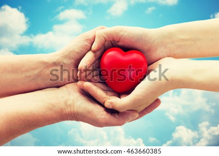 people, age, family, love and health care concept - close up of senior woman and young woman hands holding red heart over blue sky and clouds background #463660385