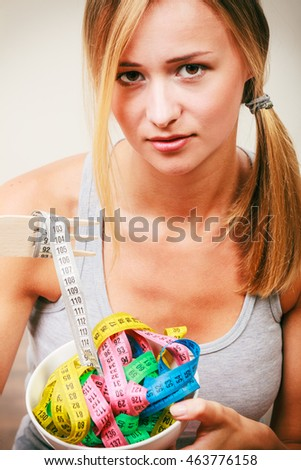 Diet, healthy eating, weight loss and slim body concept. Fit fitness girl holding bowl with many colorful measuring tapes #463776158