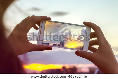 Woman hand taking photo of the city with a smartphone. Close up of woman's hands. Cell phone. Telephone. Mobility and modern lifestyle concept. Beautiful sky. Young Girl Taking Photos Of Landscape
