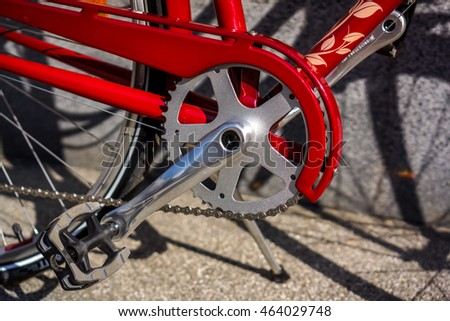 New silver crankset with new chain against part of new red city bicycle against dark background in sunshine with shadows #464029748